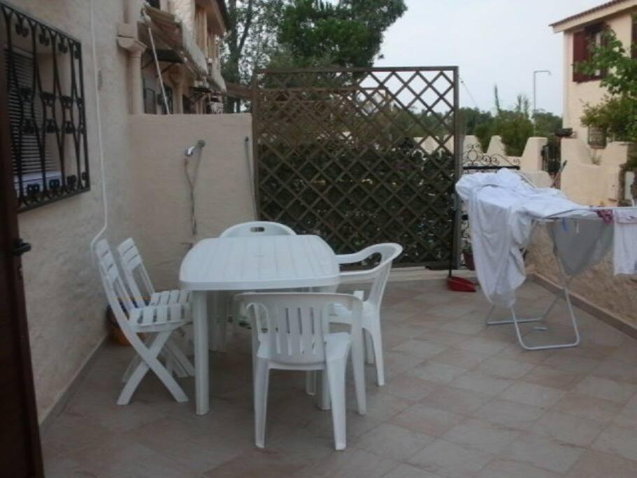 Accesso indipendente con veranda e doccia esterna. Tavolo e sedie con tenda solare