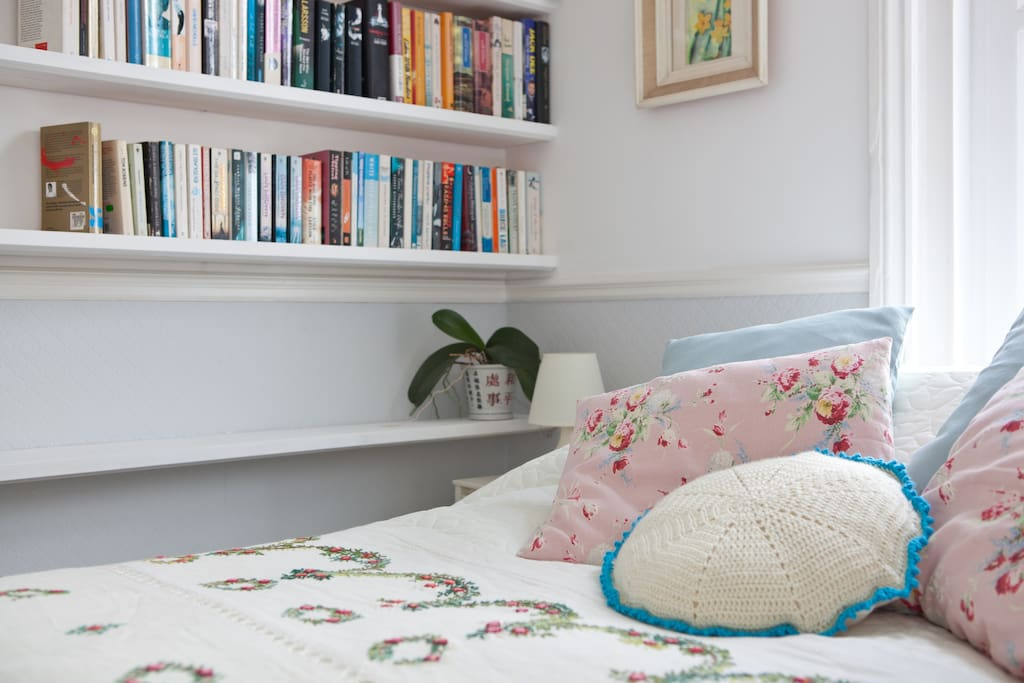 Bedroom with bookshelves and hand made cushions.