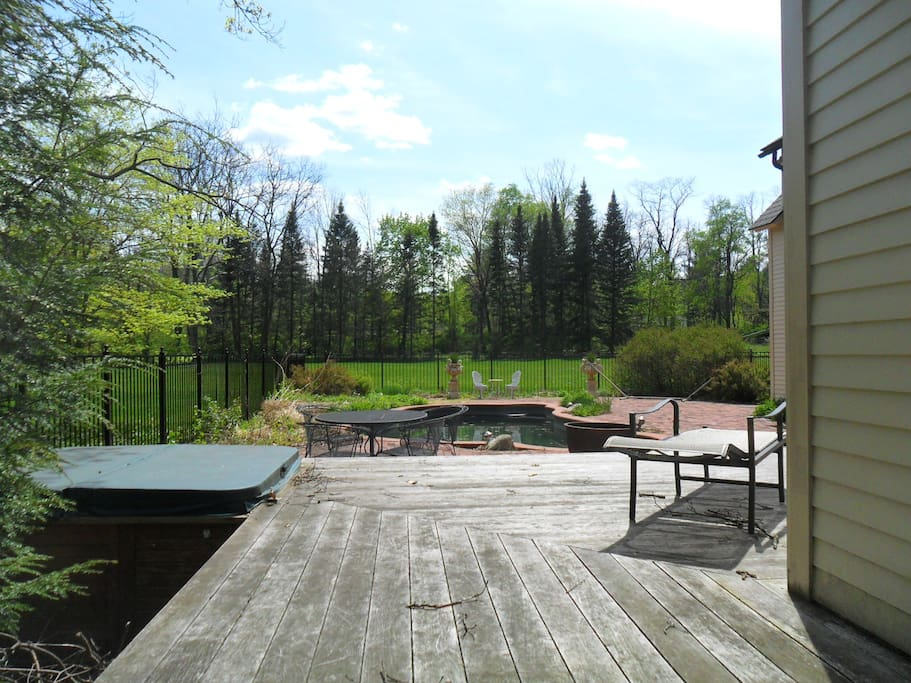 looking across deck to pool and patio. Hot tub to the left of deck.