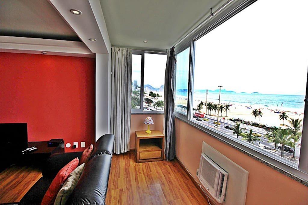 Linda sala com vista panorâmica da praia de Copacabana.