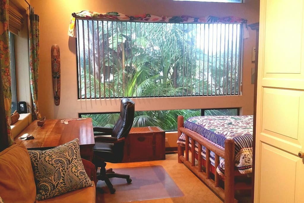 View from entry of generously-sized room.  Large 4' x 10' picture window with blinds showing view of tropical palms and giant bird of paradise just outside.  Tropical hardwood desk back left and sofa with wardrobe/TV in foreground.