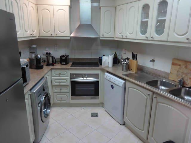 Kitchen with dish washer, washing machine, hob, oven, micro wave and nespresso machine.