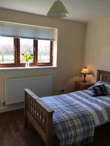 Spacious downstairs bedroom with a single bed. Bedside cabinet with lighting.