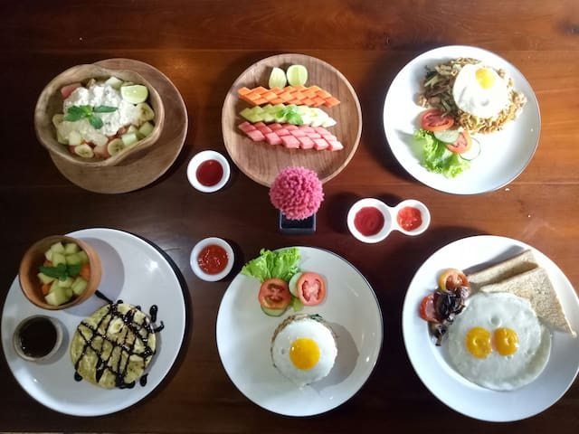Breakfast in Cafe the Daun. menu:Duo eggs,chicken fried rice,chicken fried noodle,bircher muesli,banana pancake,grilled honey banana&toast,fruits salad,vegan rice paper roll all served with watermelon juice or pineapple juice.