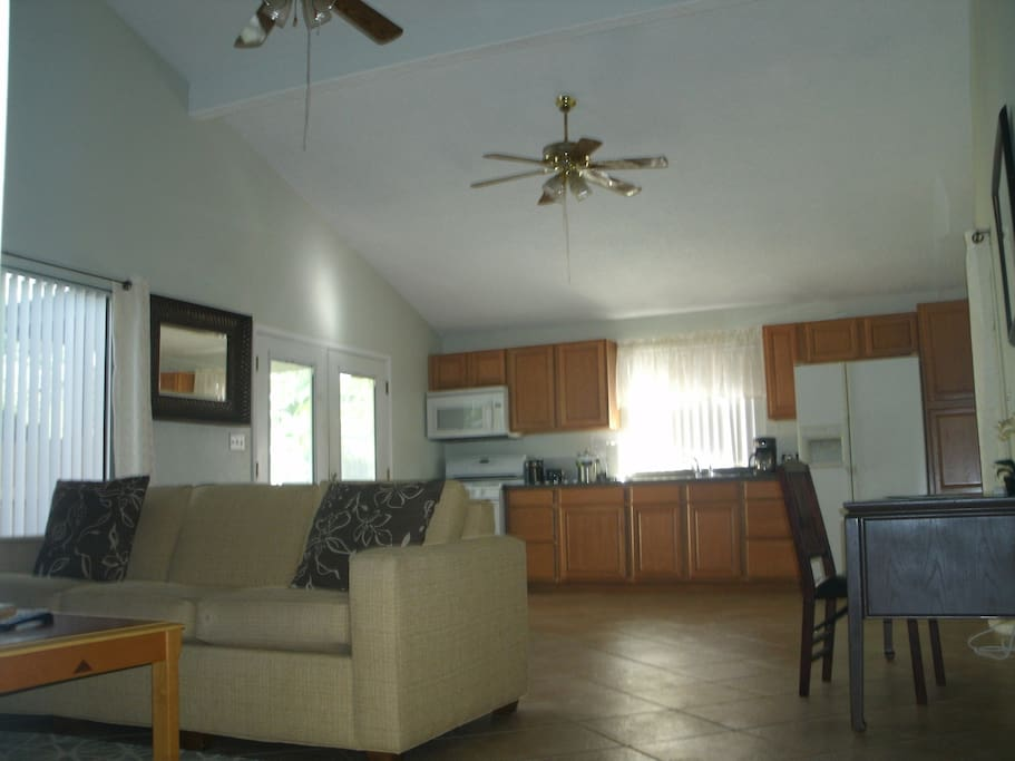 Living area open to kitchen, dining and high vaulted ceilings.