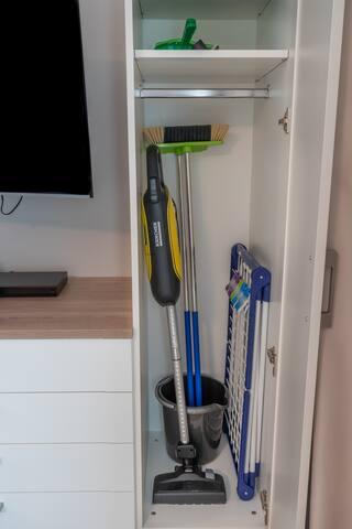 Die Reinigungsutensilien neben dem Fernseher. (Staubsauger, Besen, Kehrblech, Eimer, Wischer und Wäscheständer sind vorhanden.)