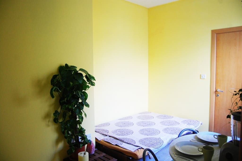 The yellow room from a different angle with the double-bed and the entrance.
