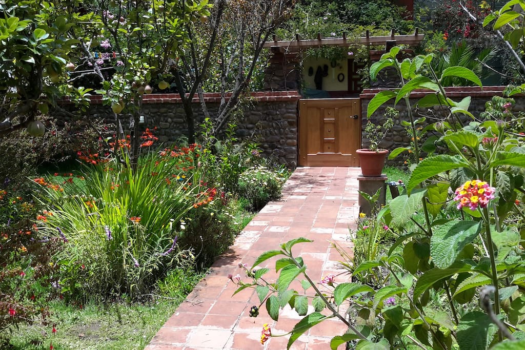 River rock wall encloses the lush garden full of fruit trees and flowers.