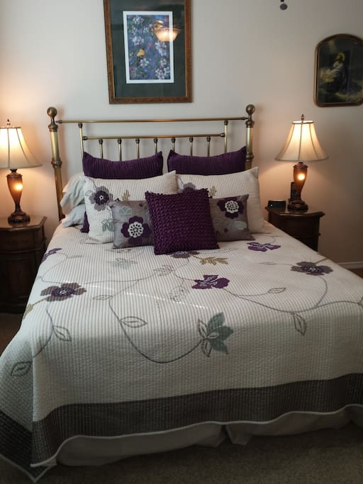 Comfortable queen sized bed with night stands and individual reading lights