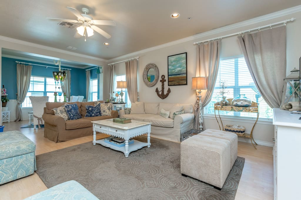 Bright, open-concept living area with a pair of comfy couches and a dining table for 8.