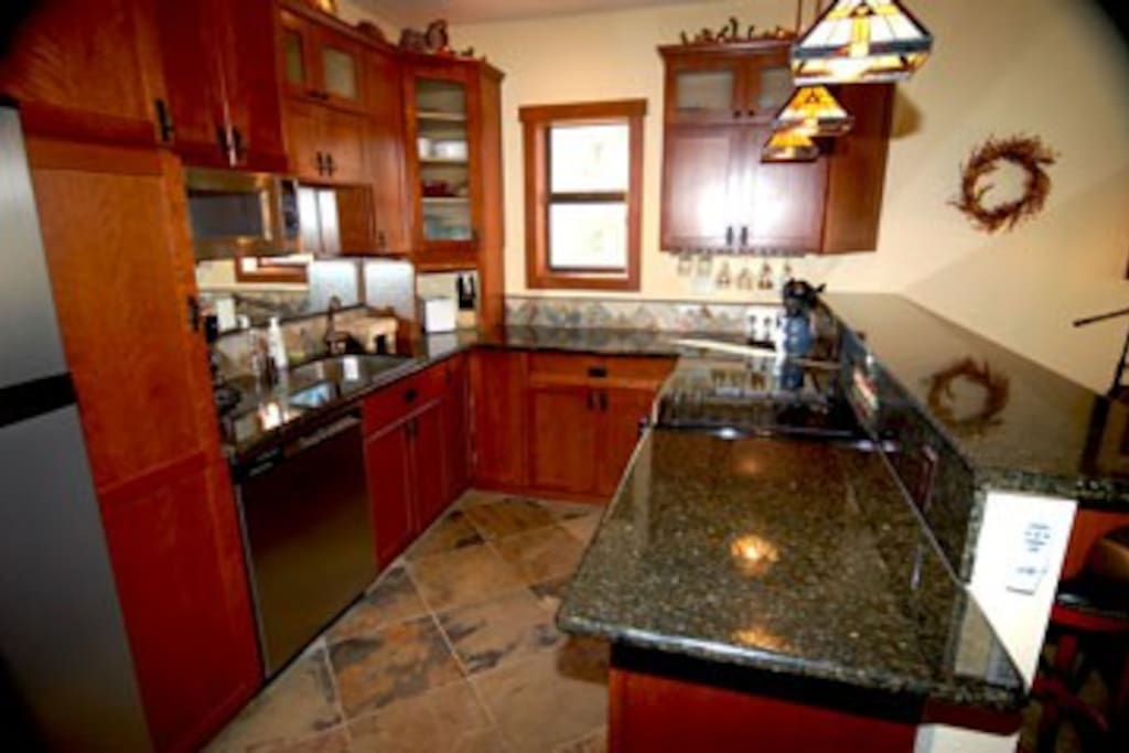 Granite-topped kitchen is fully equipped, features modern appliances, and also gives gorgeous Lake view.