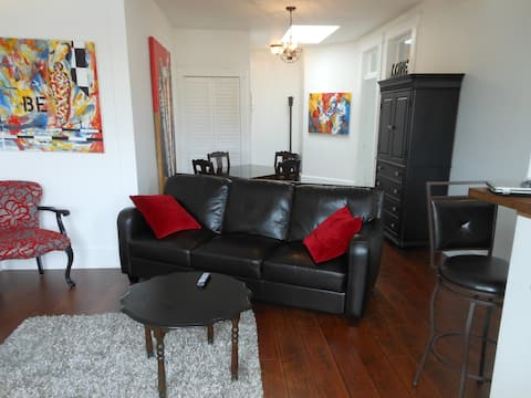 Open concept living/dining area with industrial style skylight in entrance and heritage transom doors throughout