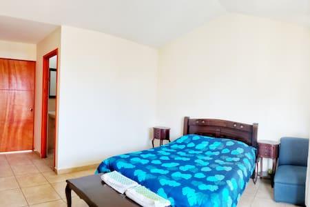 Habitacion privada, con cama doble, baño privado, televisor, ventilador, armario, balcon.