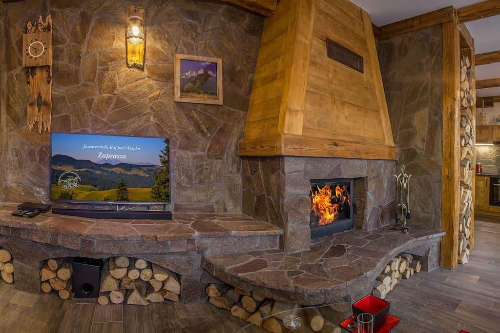 Komfortowy salon z kominkiem wykończony w drewnie i naturalnym kamieniu.  Zaprojektowany i urządzony z pomocą lokalnych artystów.