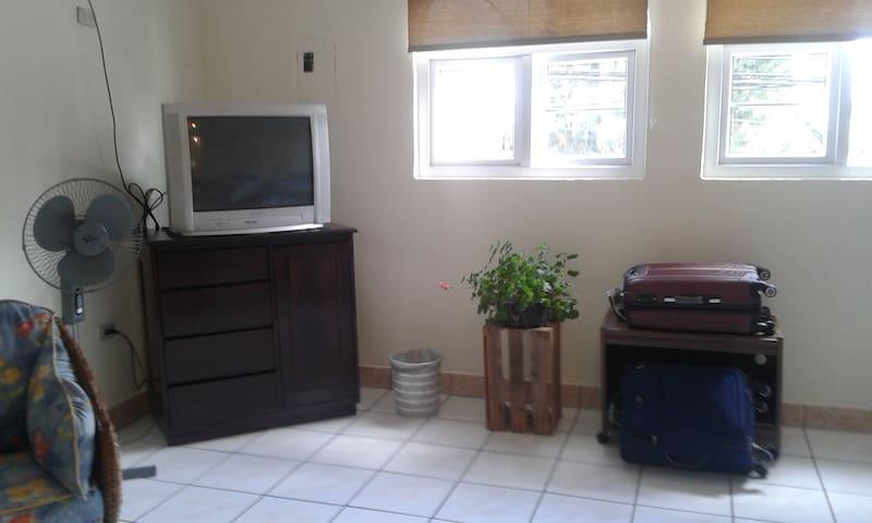 habitación con tv, espaciosa dos ventanas que proporcionan ventilación y entrada de luz, cajon para ropa, ventilador, dos sillas cómodas