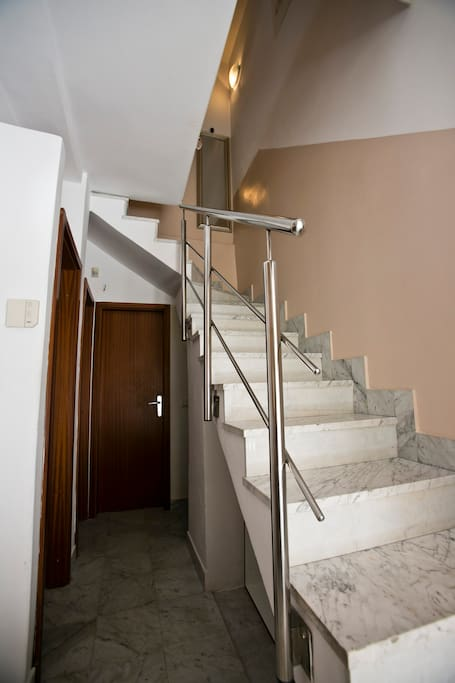 Hallway with stairs leading on the second floor on which are situated living and dining room with a kitchen and the bathroom