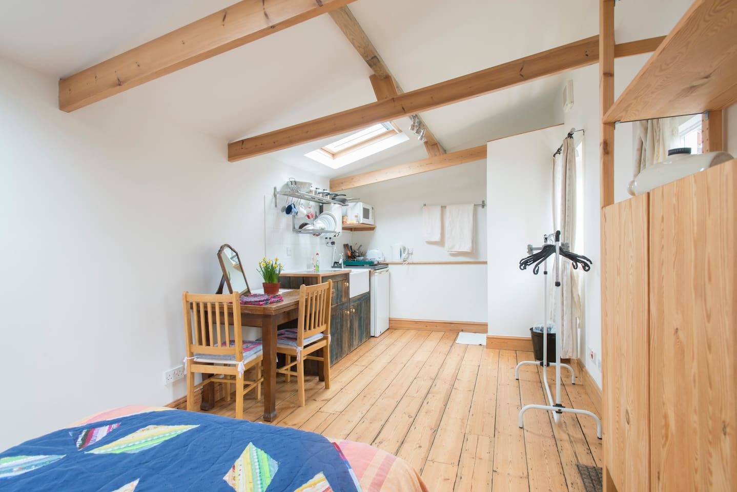 NB Airbnb photos use wide angle lenses! Compact but light and airy kitchen, dining and sleeping area with shower in far right corner