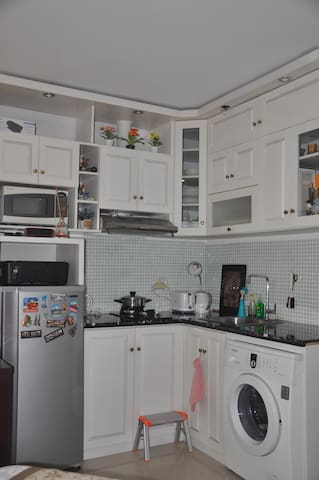 Kitchen with marble top table, amenities, fridge and front load washing machine attached to the kitchenset.