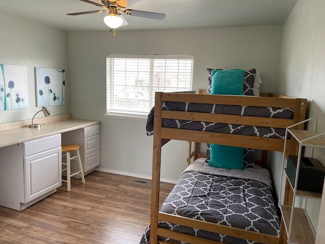 Well-lit upstairs bunk room features two twin beds and plenty of counter space for work, crafts and playtime. Built-in closet includes hanging space. Bathroom is just across the hall. Craft supplies and toys are available for ages 2-12.