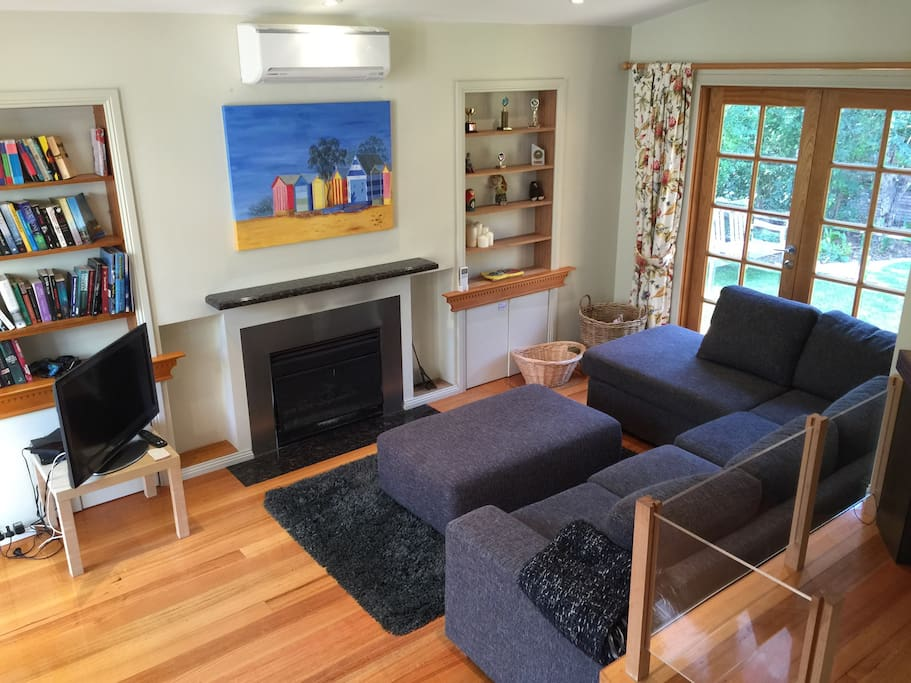 First living room with open fireplace and reverse cycle cooling and heating. 32inch LCD TV, DVD and stereo. Book collection. Fire wood hidden behind doors near the fireplace
