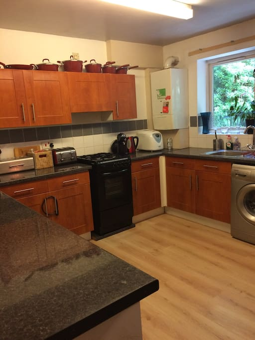 Kitchen with washing machine, cooker, microwave, food blender, coffee machine and bread machine.