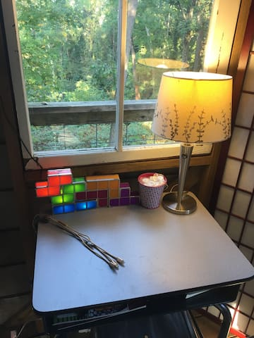 "Here's a view of the desk located on the second floor of the treehouse. I chose a school desk because I want our guests to feel youthful and be reminded of what it was like to be full of wonder and curiosity. You can open or close the window. It's magical to have it open and feel surrounded by trees.   Imagine ""working from home"" at this little desk with that view of the trees. It's such a cozy spot--one of my favorite in all of Richmond."