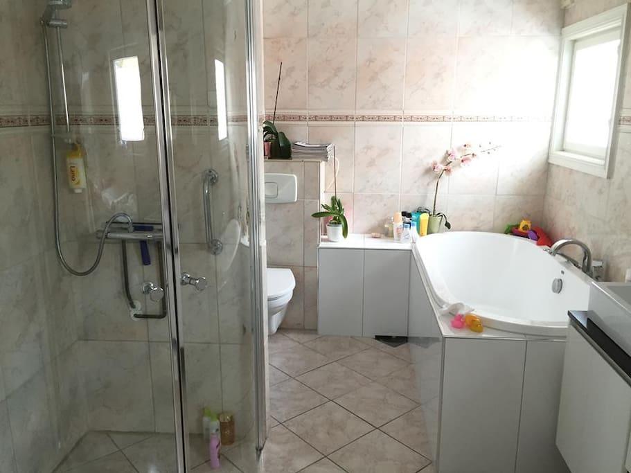 A spacious bath room with shower and bath tub