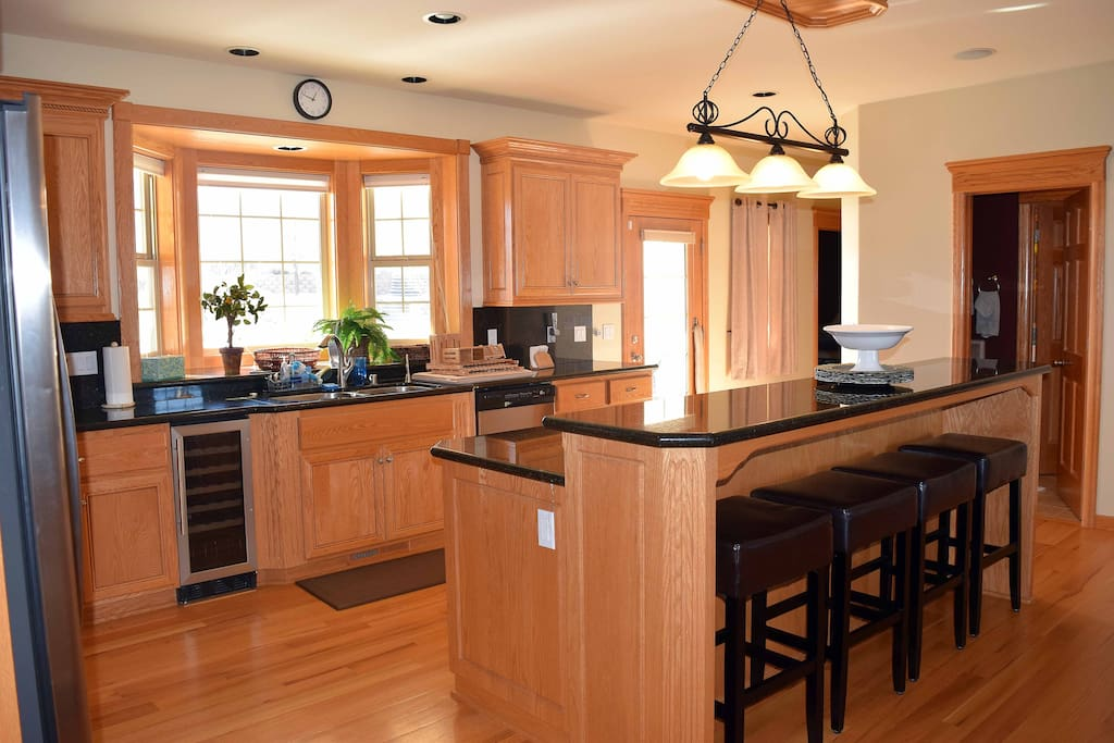 Large kitchen with all wood floors and granite counter tops with breakfast bar and fully stock cooking supplies
