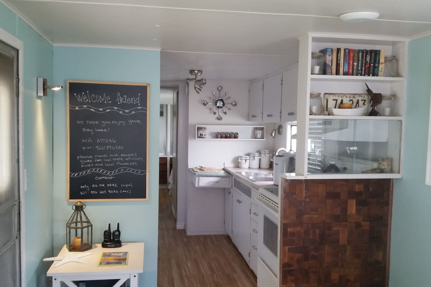 View into the kitchen. Glass top oven, refrigerator, microwave.