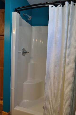 The stand-up shower is extra large, with shelves and seating for you and your soaps.