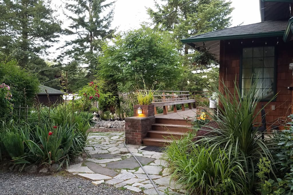 """There are four entrance steps to home, wrap around seating on deck, surrounded by many beautiful gardens """"rooms"""" on this one acre hideaway"""
