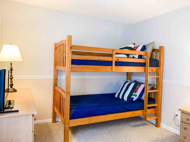 Comfortable guest bedroom with fresh linens and bright window overlooking the pool area, large double closet and TV.