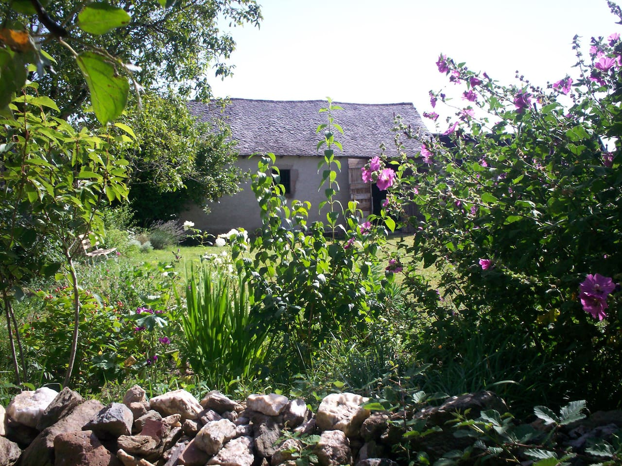 View of the vaulted barn through the garden
