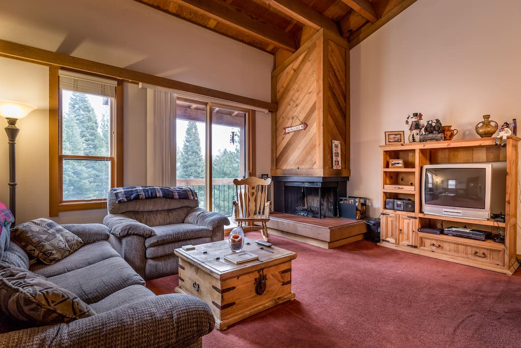 Living Room, wood burning fireplace, vaulted ceilings, glass slider out to balcony with gas bbq and views over meadow
