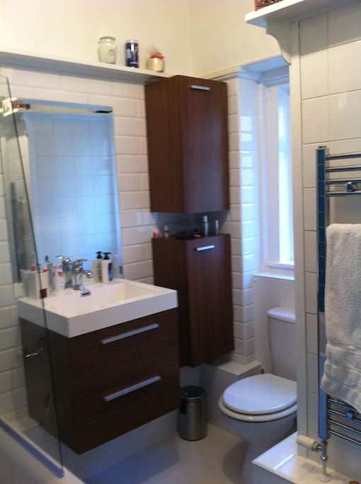 Bathroom with shower and bath, washing machine, towels provided.
