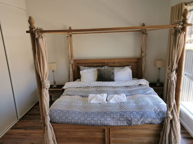 Master bedroom with gorgeous Teak timber 4 poster bed and duck down quilt.
