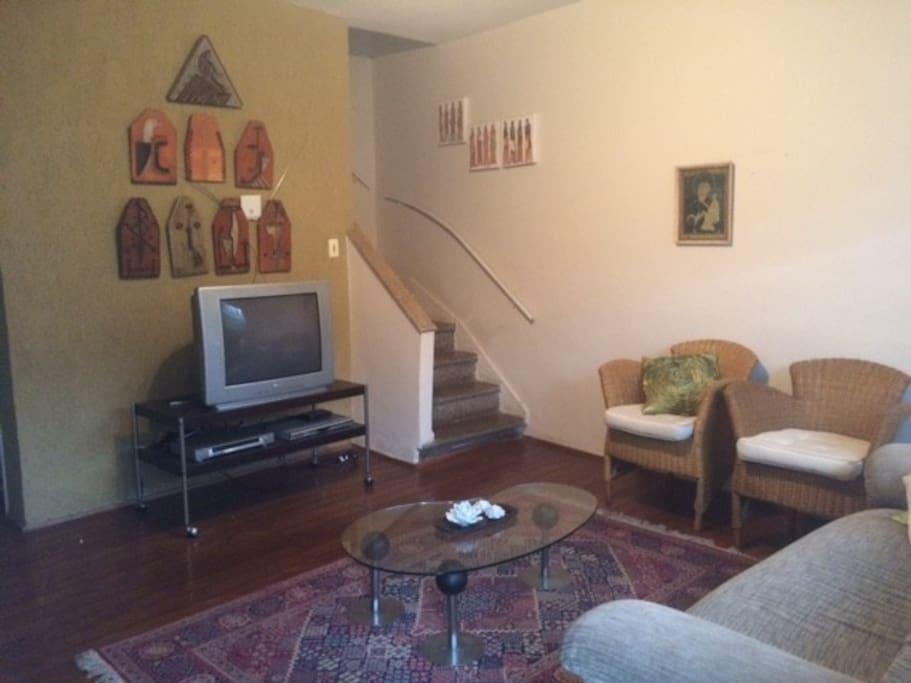 A sala tem televisão, um aconchegante sofá e poltronas