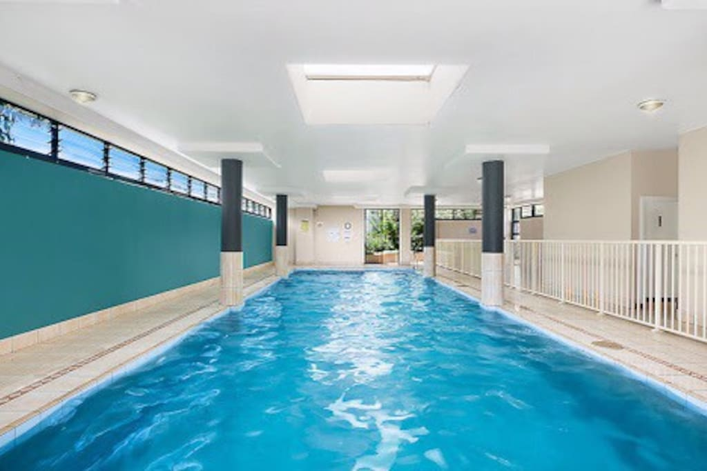 An indoor heated swimming pool with a separate spa.