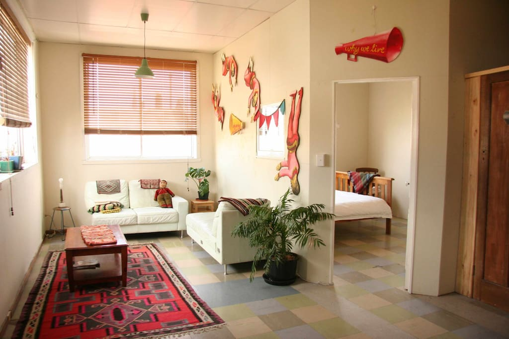 Spacious bedroom and lounge/extra sleeping area. Circus decor, sunlight, sofas and space; a recipe for relaxation.