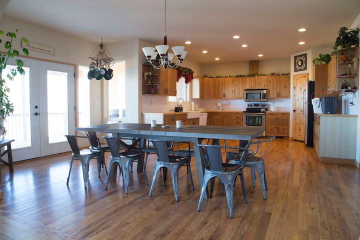 Guest dining area (seats 10) with huge, equipped kitchen and French doors leading to deck with BBQ and patio furniture that seats 4