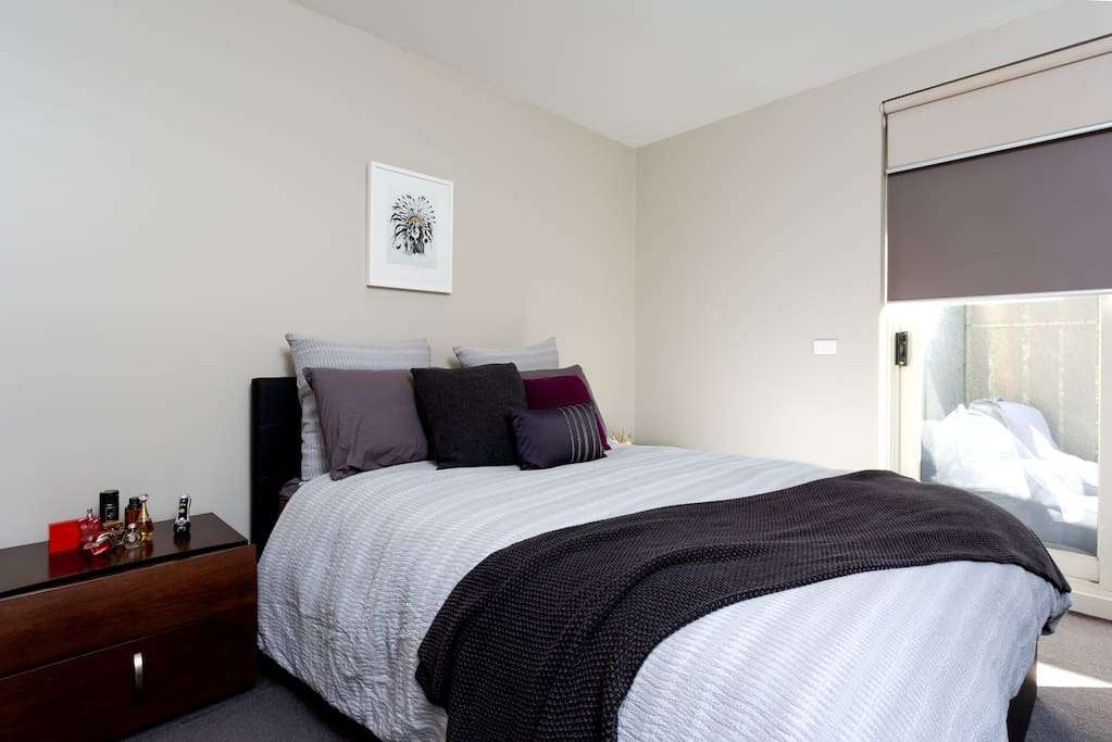 The master bedroom, complete with luxurious bedding, pillows, cushions and linen. Ample storage for all your belongings, ensuite bathroom and direct access to the balcony.