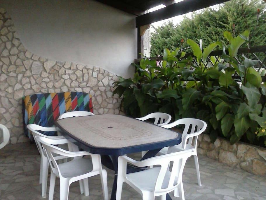 Spazio Esterno Coperto da Veranda in Legno , dove si trova Tavolo con Sedie , Divano , Lavatrice e TV.