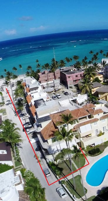 areal view of the way to the white sanded beach with sunloungers and palm tree roofs (palapas)
