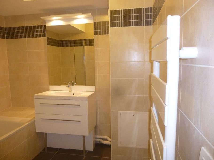 Salle de bain avec baignoire et chauffe serviettes