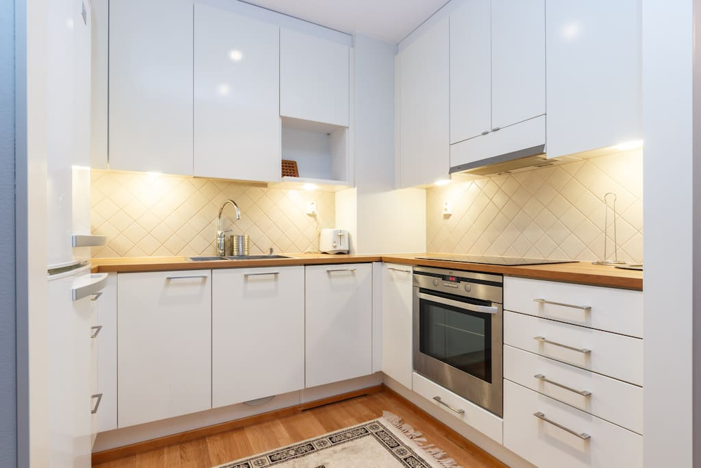 A modern, white kitchen has a dish washer, a modern oven, an induction stove and everything else you need for cooking or fixing a breakfast like microwave, a kettle, a coffee maker.