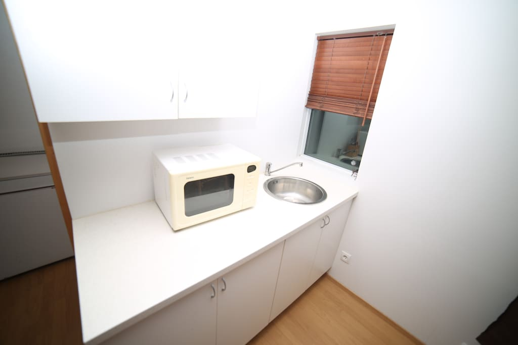 The kitchen nook is equipped with a refrigerator and basic cooking tools.