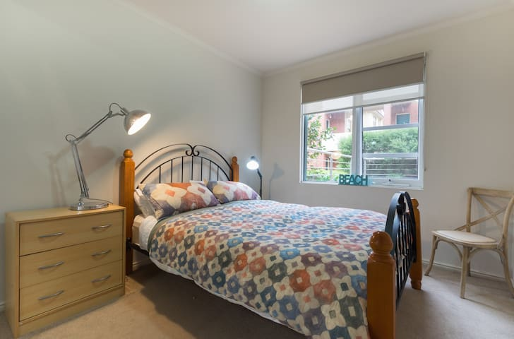 Light spacious 2nd queen bedroom with window that catches the sea breezes in summer