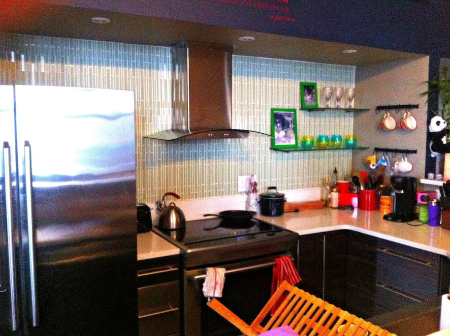 Beautiful kitchen with a double oven, exhaust hood, and an electric stove.