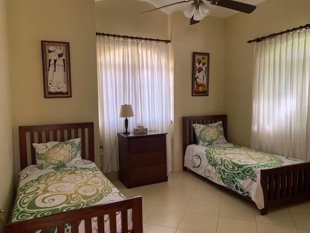 2nd bedroom w/ en suite bath, AC, ceiling fan, TV and walk in closet.