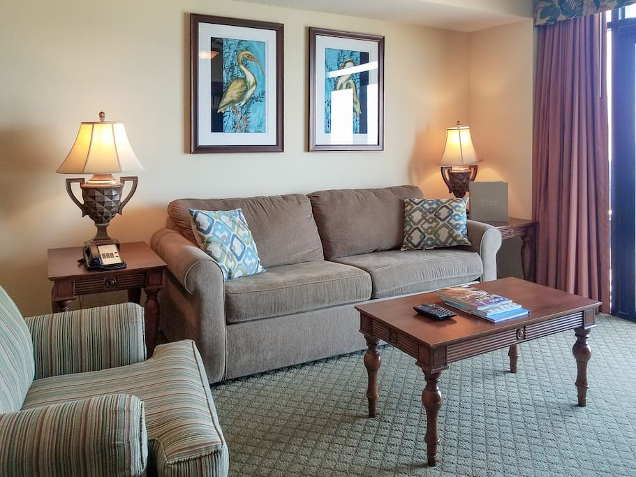 The living area offers plenty of comfy seating with 2 armchairs and a plush sleeper sofa.
